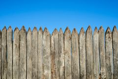 Fence made of sharp wooden stakes against the blue sky. Wooden fence vertical logs pointed against the sky protection against inva. Ders and wild animals stock photos
