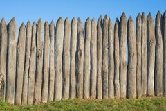 Fence made of sharp wooden stakes against the blue sky. Wooden fence vertical logs pointed against the sky protection against inva. Ders and wild animals stock photo