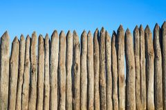 Fence made of sharp wooden stakes against the blue sky. Wooden fence vertical logs pointed against the sky protection against. Invaders and wild animals royalty free stock images