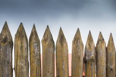Fence made of sharp wooden stakes against the grey sky. Fence made of sharp wooden stakes against the grey cloudy sky stock images