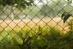 Fence made of wired steel designed in colander with blurred rural football field in background stock photography