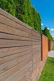 Fence made of wood and bricks. Live fence of tui trees. A sunny day in a country town Royalty Free Stock Image