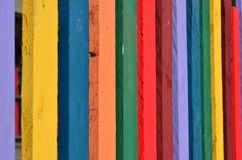 Fence made from colorful wooden planks. Fence made from wooden planks painted in different vivid colors. Angle view. Background stock image