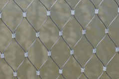 Fence Mesh. A closeup photo taken on a fence mesh against a lake royalty free stock photography