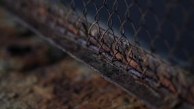 The fence mesh is covered with rust. Corrosion of metal. Harmful effects of oxygen and water on the metal. Iron rust. Oxidation of metals. Hole in the fence stock video footage