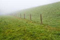 Fence with mesh and wooden poles beside a dike Stock Image