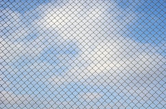 Fence metallic net and cloudy sky Royalty Free Stock Image