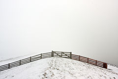 Fence on a misty, snowy dike Stock Photography