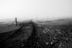 A fence on a mountain in the midst of fog.  stock photo