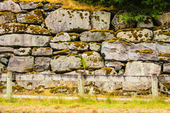Fence and narrow path along wet stone wall Stock Photo