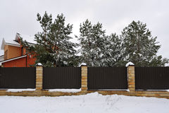 Fence near the house with pines, in winter Stock Photo