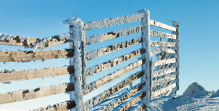Fence near mountain slope covered by heavy snow on a sunny winter day royalty free stock photos