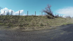 Fence near road spring. Camera on steadicam on road by fence hill stock footage