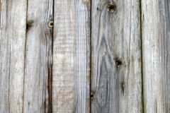 Fence of old unpainted boards for a background. Closeup Royalty Free Stock Photos