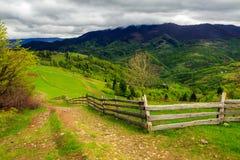 Fence On Hillside Meadow In Mountain Stock Photo