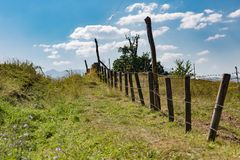 Fence, path, and clouds meeting behind a green hill Stock Images