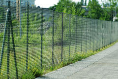A fence with a pedestrian way. And a green site royalty free stock photos