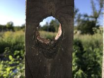 Fence peg with a natural hole view of nature.  royalty free stock photography