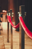 Fence pole attached with red rope Red carpet Royalty Free Stock Image