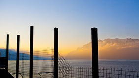 Fence Pole Silhouetted. Silhouette fence pole with Lake Geneva and Chablais Alps in the background Stock Photography