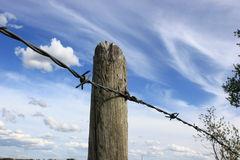 Fence Post. With barbed wire against a blue sky Stock Images