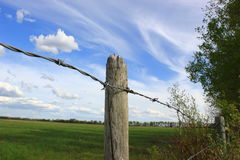 Fence Post. With barbed wire in a field Stock Image