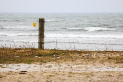 Fence post by stormy sea in Gotland Royalty Free Stock Images