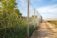 The fence protecting the border between Hungary and Serbia. ROESZKE, HUNGARY - SEPTEMBER 15: View on the 175km long fence between Hungary and Serbia installed Royalty Free Stock Photography