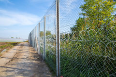 The fence protecting the border between Hungary and Serbia. ROESZKE, HUNGARY - SEPTEMBER 15: View on the 175km long fence between Hungary and Serbia installed Stock Photos