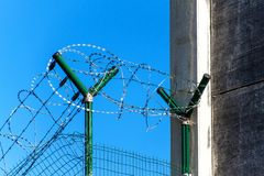 Fence with razor barbed wire. Guarded area. Military base. Razor wire. Stock Photo