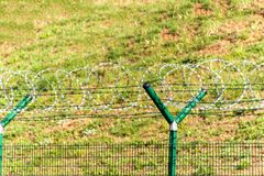 Fence with razor barbed wire. Guarded area. Military base. Razor wire. Royalty Free Stock Images