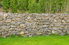 Fence real stone wall surface with cement on green grass field Stock Photography