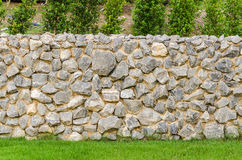 Fence real stone wall surface with cement on green grass field Royalty Free Stock Image