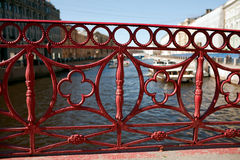 Fence red iron bridge in St. Petersburg. Iron red fence of the bridge in St. Petersburg stock images
