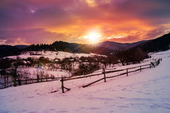 Fence by the road to snowy forest in the mountains Stock Image