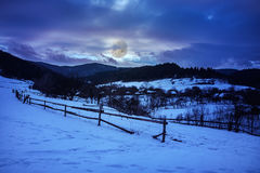 Fence by the road to snowy forest in the mountains Royalty Free Stock Images