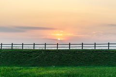 Fence, rural nature at sunset. Beautiful summer landscape with field Stock Photos