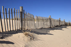Fence on Sand Dune. Rail Fence partially Buried on Sand Dune Royalty Free Stock Photography