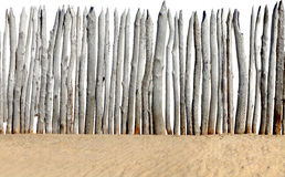 Fence on sand isolated. Old wooden fence on the sand isolated on the white background royalty free stock photo