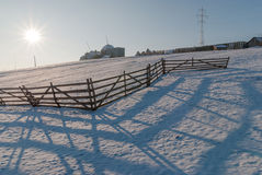 The fence of a sheep fold and a sheep cot in a winter scene. Beautiful sun on the sky Stock Image