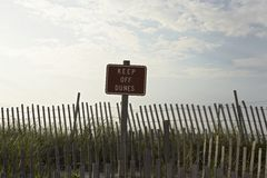 Fence and sign reading 'keep off dunes' Royalty Free Stock Photo