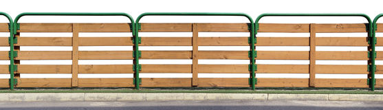 The fence of a small urban school stadium isolated. The fence of a small urban school stadium is made of green metal pipes and wooden boards. Isolated on white Stock Photography