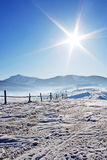 Fence in snow covered mountain under blue sky. Wooden fence in snow covered mountains under shiny sun Royalty Free Stock Photo