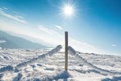 Fence with snow in winter alpine village Royalty Free Stock Photos