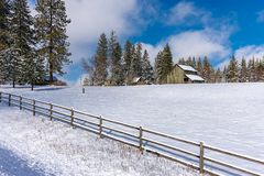 Fence by snowy field and barn. Stock Images
