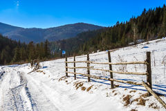 Fence on snowy mountain slope near the forest in winter Stock Images