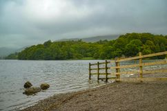 Fence and stones in the water at Grasmere lake stock photo