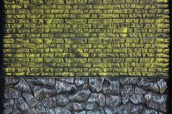 Fence texture of elongated colored stones in warm colors. Weathered stained modern fence type. Colored relief concrete wal. L royalty free stock photos