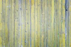 Fence thin slats with a cracked yellow paint. Background of wooden boards. Blank background with texture stock photo