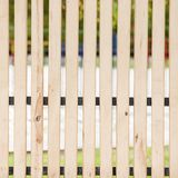Fence of thin wooden boards between which the gap. Fence of thin light wooden boards between which the gap stock image